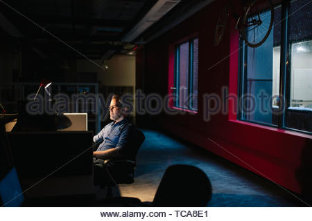 Engagierte Unternehmer spät in dunklen Büro arbeiten Stockbild