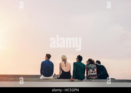 Rückansicht des jungen Freunde sitzen zusammen auf der Dachterrasse bei Sonnenuntergang. Junge Männer Stockbild