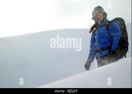 Eine Frau, die zu Fuß in einen Schneesturm Stockbild
