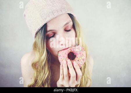 Portrait einer jungen und lustige blonde Frau isst eine rosa Donut Stockbild