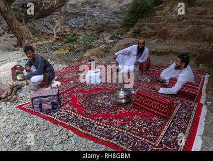 Saudische Männer, Picknick im Wadi lajab, Provinz Jizan, Jebel Qahar, Saudi-Arabien Stockbild