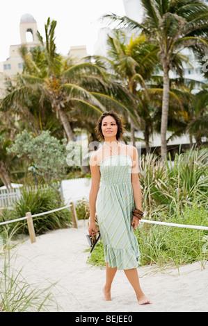 Junge Frau hält Pantoffel und Wandern am Strand Stockbild
