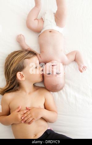 Schwester küssen ihre jüngeren Geschwister Stockbild