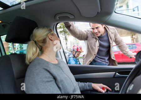 Mann im Gespräch mit Frau während sie Auto fährt Stockbild