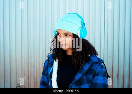 Junge Teenager Frau Musik vor einer blauen Wand Stockbild