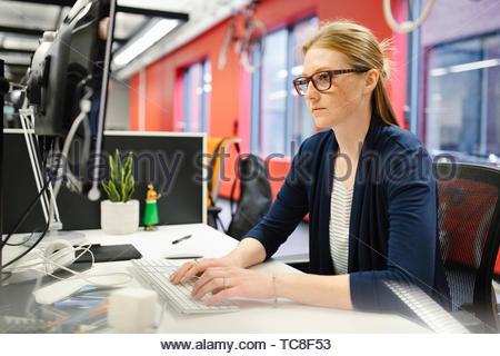 Geschäftsfrau, die Arbeiten am Computer im Büro konzentriert Stockbild