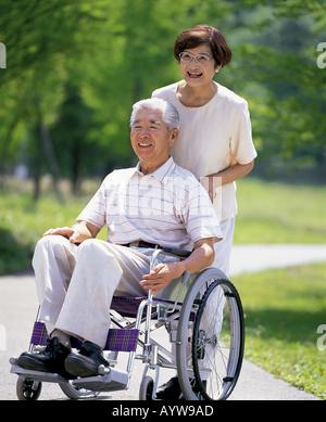 Sinior Frau ihrem Mann im Rollstuhl schieben Stockbild