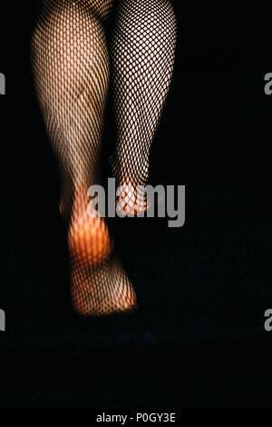 Ansicht von hinter einer Frau zu Fuß mit schwarzen Netzstrumpfhose Strümpfe Stockbild