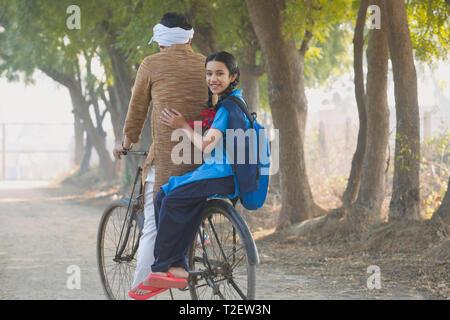 Rückansicht eines happy School Girl Sozius reiten auf dem Fahrrad mit Ihrem Vater im Dorf. Stockbild