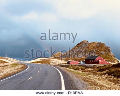 Ein Regenbogen über eine einsame Straße bis in die Hügel Stockbild