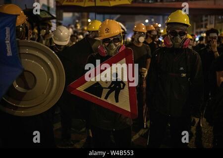 Die Demonstranten bereit Bereitschaftspolizei mit improvisierten Schilde zu Gesicht. Die Demonstranten mit den Hong Kong Polizei am Ende der bürgerlichen Menschenrechte vor März. Hong Kong Demonstranten versammelten für ein weiteres Wochenende der Proteste gegen die umstrittene Auslieferung Rechnung und mit einer wachsenden Liste von Beschwerden, die der Aufrechterhaltung des Drucks auf Chief Executive Carrie Lam. Stockbild