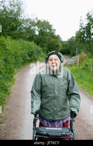 Lächelnd senior Woman walking Frame auf Weg Stockbild
