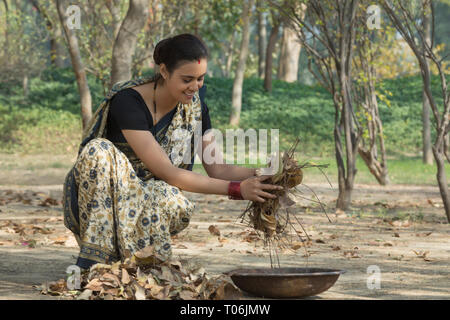 Ländliche Frau, gekleidet in Saree sammeln getrocknete Blätter vom Boden in einem Eisen Gold Pan. Stockbild