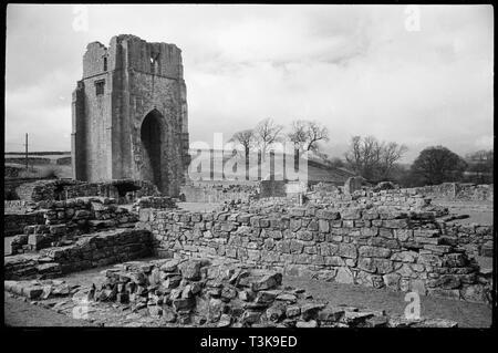Shap Abtei, Cumbria, c 1955 - c 1980. Ein Blick auf die zerstörte Shap Abtei, zeigt die niedrige Wände und die West Tower im Hintergrund, von Süden gesehen - Osten, möglicherweise aus dem Osten Bereich der Kreuzgang. Die Abtei liegt westlich von Shap Village, entlang des Flusses Lowther entfernt und ist der Prämonstratenser Herkunft. Die frühesten Teile der Abtei sind Ende 12. bis Anfang des 13. Jahrhunderts und am westlichen Ende des Presbyteriums. Es hat einen kreuzförmigen Plan und liegt west-ost, mit einer hohen Westturm aus dem 16. Jahrhundert. Es ist ein quadratischer Turm, hat einen hohen Spitzbogen auf dem Boden und drei Stockbild