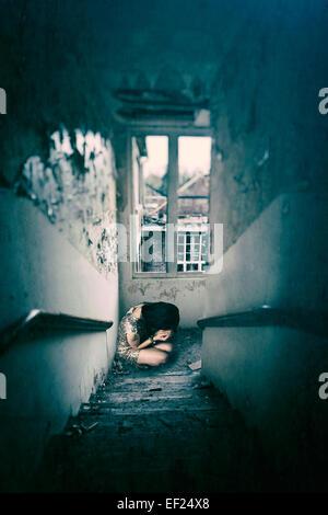 Frau Hocke in einem verfallenen Gebäude Stockbild