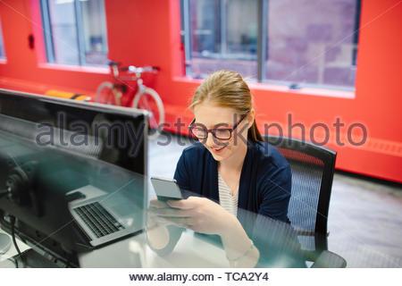 Geschäftsfrau mit Smart Phone am Computer im Büro Stockbild