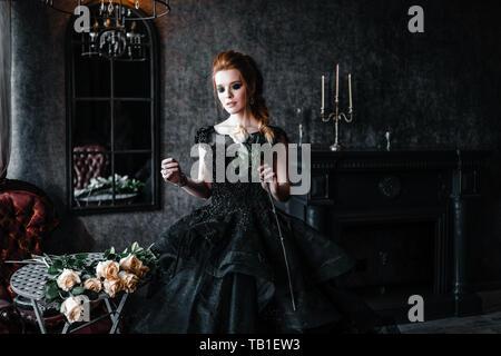 Attraktive Frau in schwarzem Kleid in mittelalterliche Einrichtung Stockbild