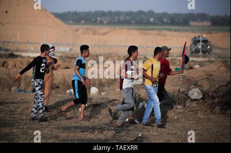 Demonstranten werden gesehen, Wanderungen in den Zaun, Gaza und Israel während der Auseinandersetzungen. Palästinenser stießen mit israelischen Truppen während einer großen Demonstration auf der Grenze zum Gazastreifen, den Aufruf für ein Ende der israelischen Belagerung von Gaza und das Recht auf ihre Wohnungen am Grenzzaun zwischen Israel und Gaza im südlichen Gazastreifen zurück. Stockbild