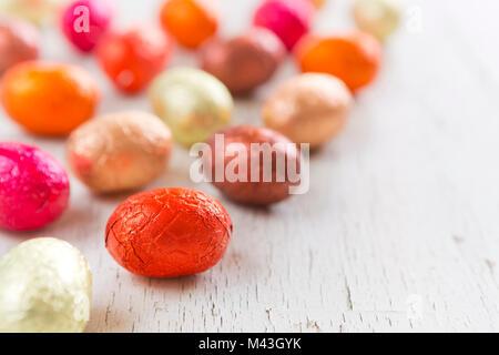 Nahaufnahme einer Auswahl an Ostern Schokoladeneier auf einem rustikalen hölzernen Hintergrund. Stockbild