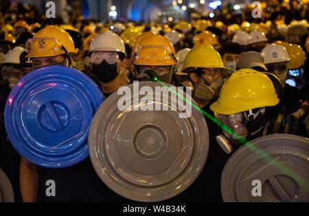 Eine Demonstrantin mit einem grünen Laser gegen die Bereitschaftspolizei Offiziere. Tausende Demonstranten nehmen Sie Teil einer Grosskundgebung fordert unabhängige Untersuchung Polizei Taktik in Hongkong. Stockbild
