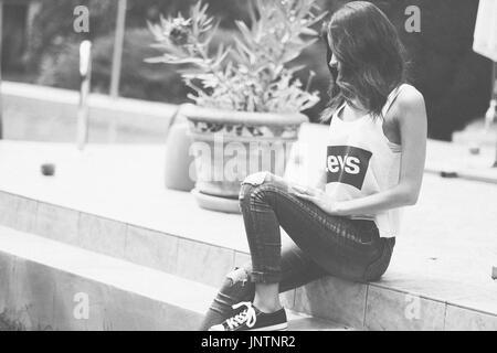 Authentische junge Frau sitzt auf der Treppe im Sommer Stockbild