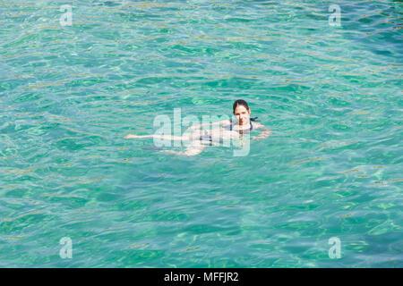 Cala Murada, Mallorca, Spanien - ein junge Frau lächelnd beim schwimmen im türkisblauen Mittelmeer in Cala Murada Stockbild