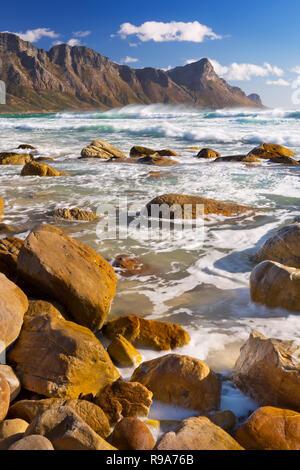 Ein felsiger Strand im Kogel Bay in Südafrika mit den Kogelberg Bergen im Rücken. Fotografiert an einem Tag sehr windig, aber sonnig. Stockbild