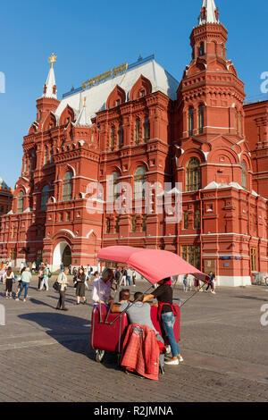 Ein Eis Verkäufer in Manezhnaya Quadrat, Moskau. Mit der Russischen Staatlichen Historischen Museum im Hintergrund. Stockbild