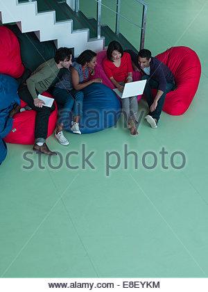 Geschäftsleute in Bohne Beutel Stühle Blick auf laptop Stockbild