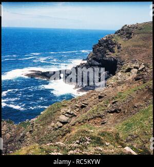 Carn Vellan, St Just, Cornwall, 1967-1970. Die Klippen am Carn Vellan und Wellen um den Natural Arch in der Ferne. Stockbild