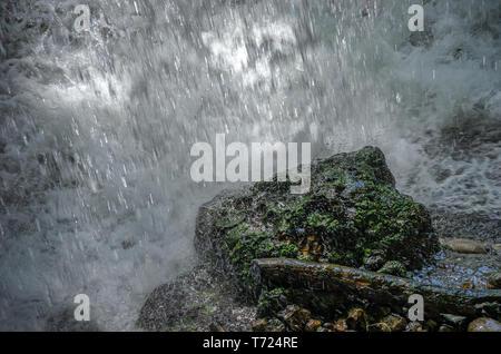 Wasser fällt auf ein Grün bemoosten Stein. Stockbild