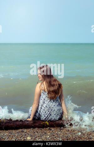 Ein Mädchen sitzen auf ein Protokoll auf einem See Stockbild