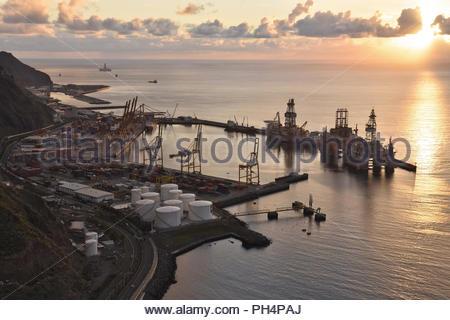 Industrial Container Port mit der bohrinsel Plattformen, Sun über den Atlantischen Ozean in Santa Cruz de Tenerife Kanarische Inseln Spanien steigt. Stockbild