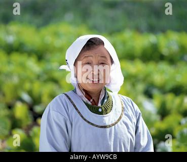 Sinior Frau mit Schürze und Tuch auf dem Kopf Stockbild