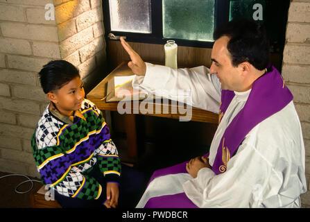 Der katholische Priester den Segen Kind mit der Hand über den Kopf des Kindes während der Abstimmung statt. © Myrleen Pearson.... Ferguson Cate Stockbild