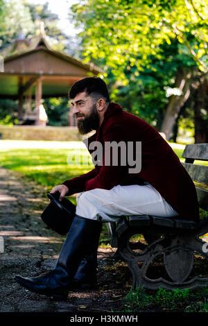 Regency gekleideter Mann sitzen auf einer Bank in einem park Stockbild