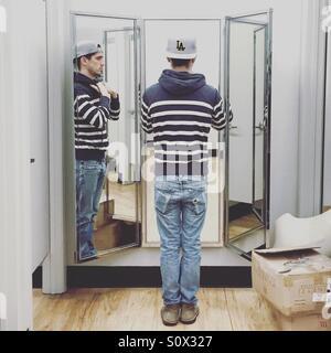 Mann im Spiegel der Umkleidekabine Stockbild