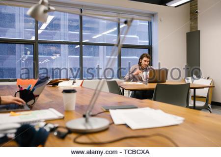 Engagierte Unternehmer spät am Laptop arbeiten, Essen nehmen Sie essen im Büro Stockbild