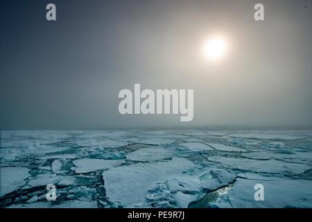 Brechen durch das Meereis, mit der Sonne hinter dem Nebel, tiefen Blau- und Grüntöne von Ocean obwohl das Eis Stockbild