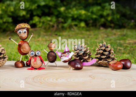 Gruppe von kleinen Zeichen oder Figuren mit Kastanien auf einem hölzernen Hintergrund an einem sonnigen Tag gemacht. Stockbild