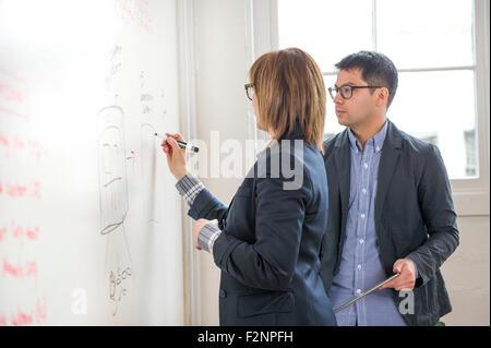 Business-Leute, die schreiben auf Whiteboard im Büro Stockbild