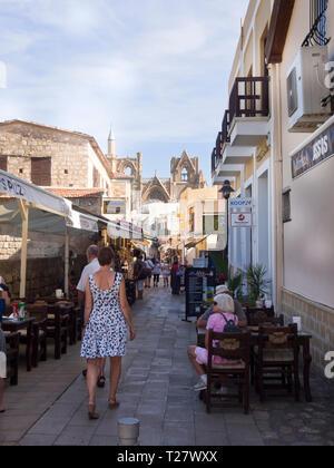 Fußgängerzone mit Touristen und Cafes in Famagusta im Norden Zyperns, Lala Mustafa Pasa Camii im Hintergrund Stockbild