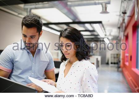 Geschäftsleute mit Laptop und Unterlagen im Büro Stockbild