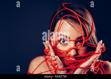 Studio geschossen von den Kopf einer Frau in Rot Wolle gewickelt Stockbild
