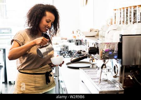 Frau barista Vorbereitung eine Tasse Kaffee in einem Café. Stockbild