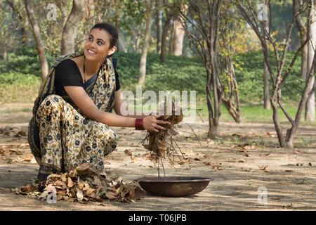 Lächelnd ländliche Frau, gekleidet in Saree sammeln getrocknete Blätter vom Boden in einem Eisen Gold Pan. Stockbild