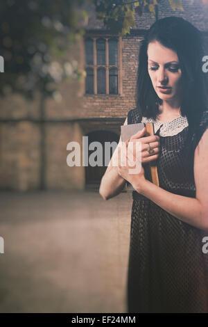 Einsame Frau, die ein Buch hält Stockbild