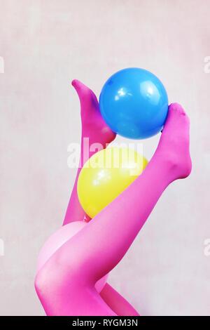 Pop Art über Beine tragen rosa Strumpfhosen und Holding Ballons Stockbild