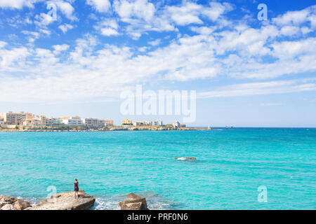 Otranto, Apulien, Italien - eine Frau, die auf einem riesigen Stein an der Küste von Otranto Stockbild