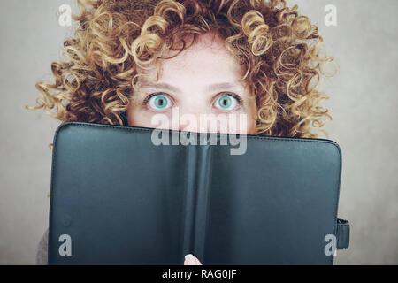 Nahaufnahme Porträt einer schönen und jungen lustige Frau mit blauen Augen und Lockige blonde Haare, sie ist hinter einer Tagesordnung oder ebook und Sie ist überrascht Stockbild